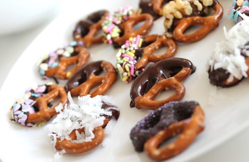 Lauryn Evarts, fitness and health blogger with dark chocolate dipped pretzels with coconut and chopped walnuts.